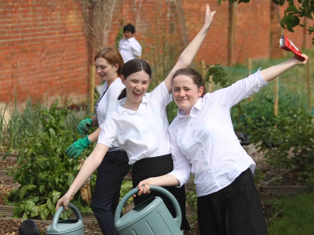 Leighton Park School Reading Berkshire Orchard girls with watering cans in garden