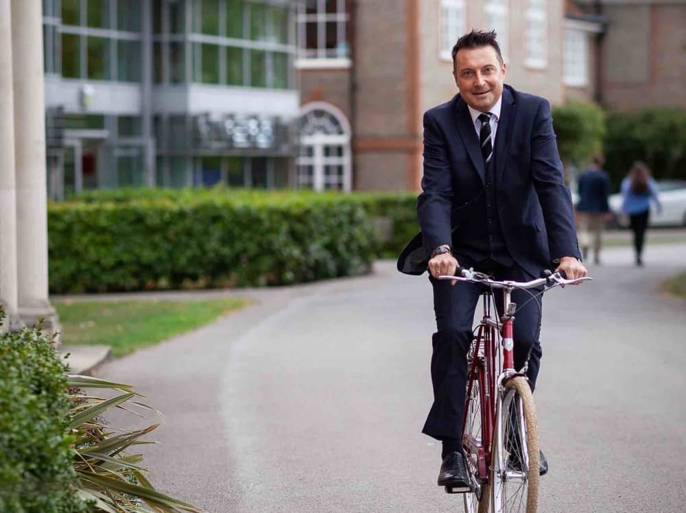 Leighton Park Reading Berkshire headteacher Matthew Juff riding his bicycle around the school grounds