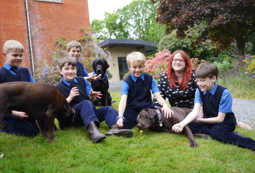 Tank tops, dogs and matron, the boys at Sunningdale School relaxing with the 'family pets'