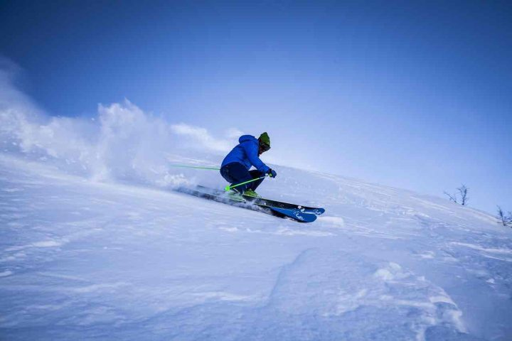 man in blue and black skiing in the soft new powder snow