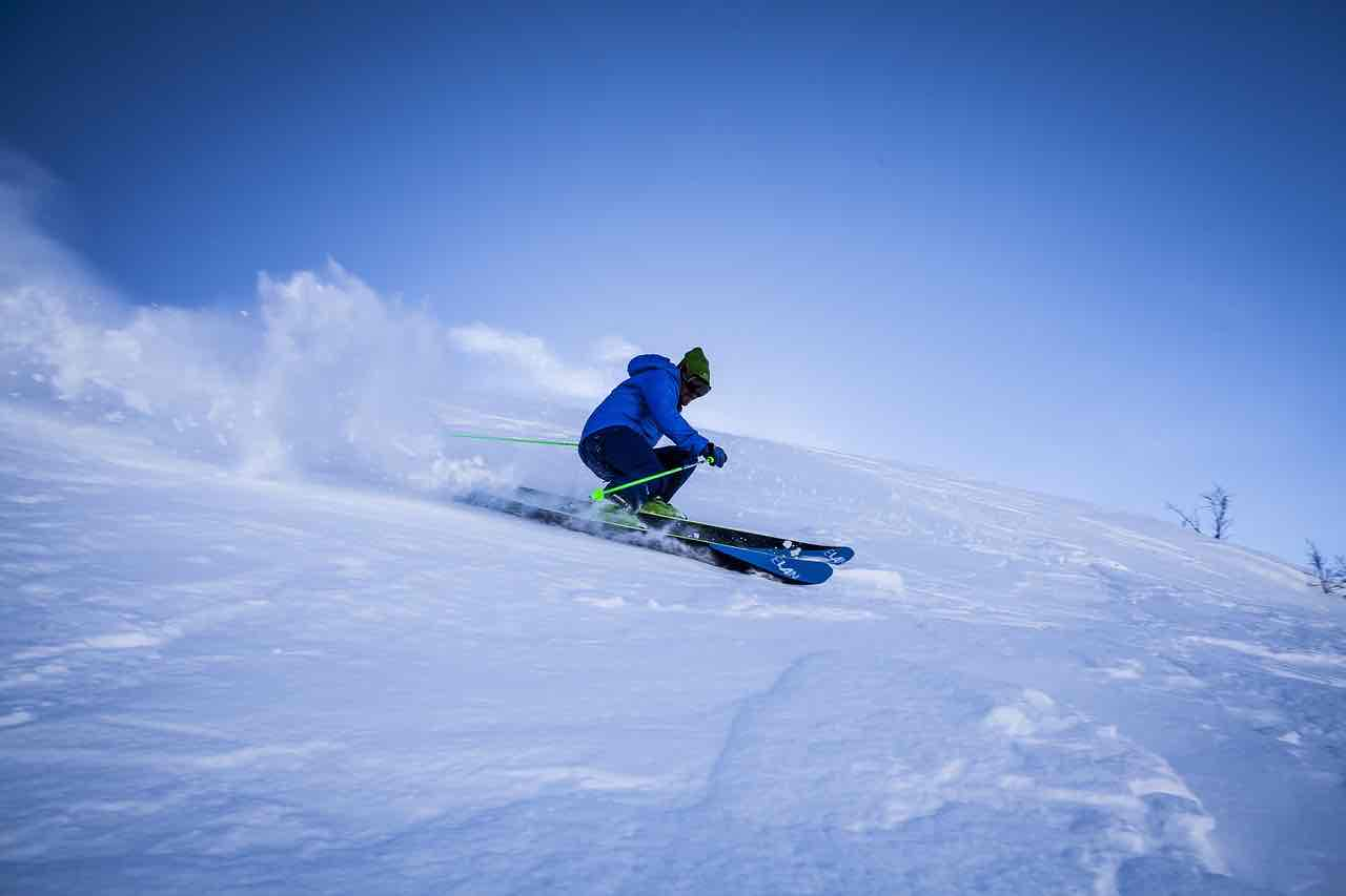 Skier in blue carving down the mountain in soft new powder snow
