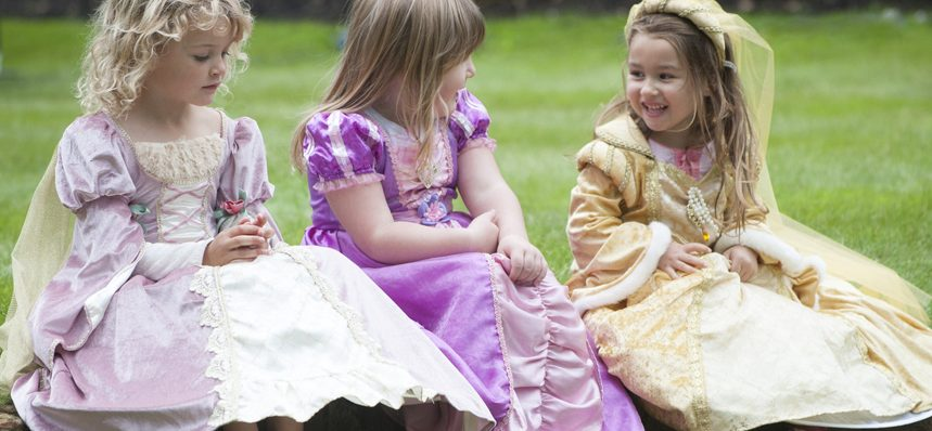 Three young girls playing dress up in royal court clothes Windsor Castle