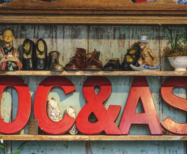 old shelving unit with vintage red letters and old children's shoes