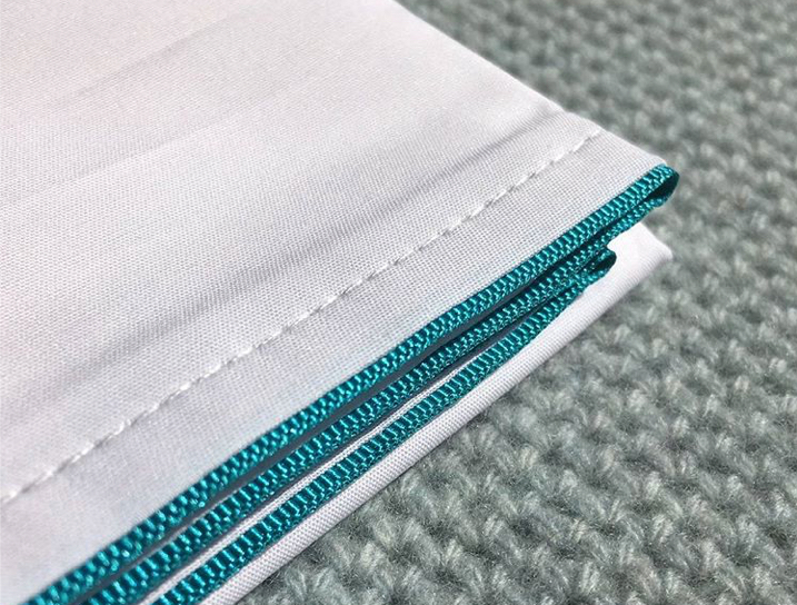 White cotton pillowcase with turquoise grosgrain trim on a duck egg chunky knit throw by Josephine Home