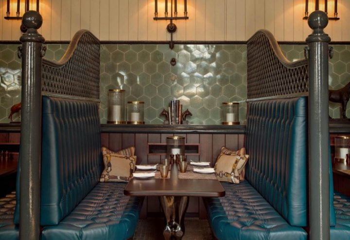 former horse stable now an elegant dining table and blue leather booth with vintage tiles ad wood panelling