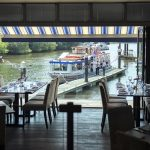 Brasserie dining room at Boulters restaurant with wooden floors, bi-folding doors opened to enjoy the river view
