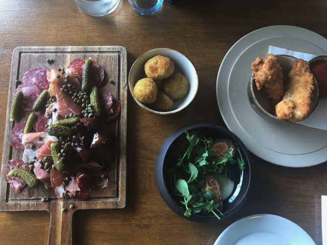 Cured meat arranged on a wooden board with small bites from the tapas menu at Boulters restaurant Maidenhead