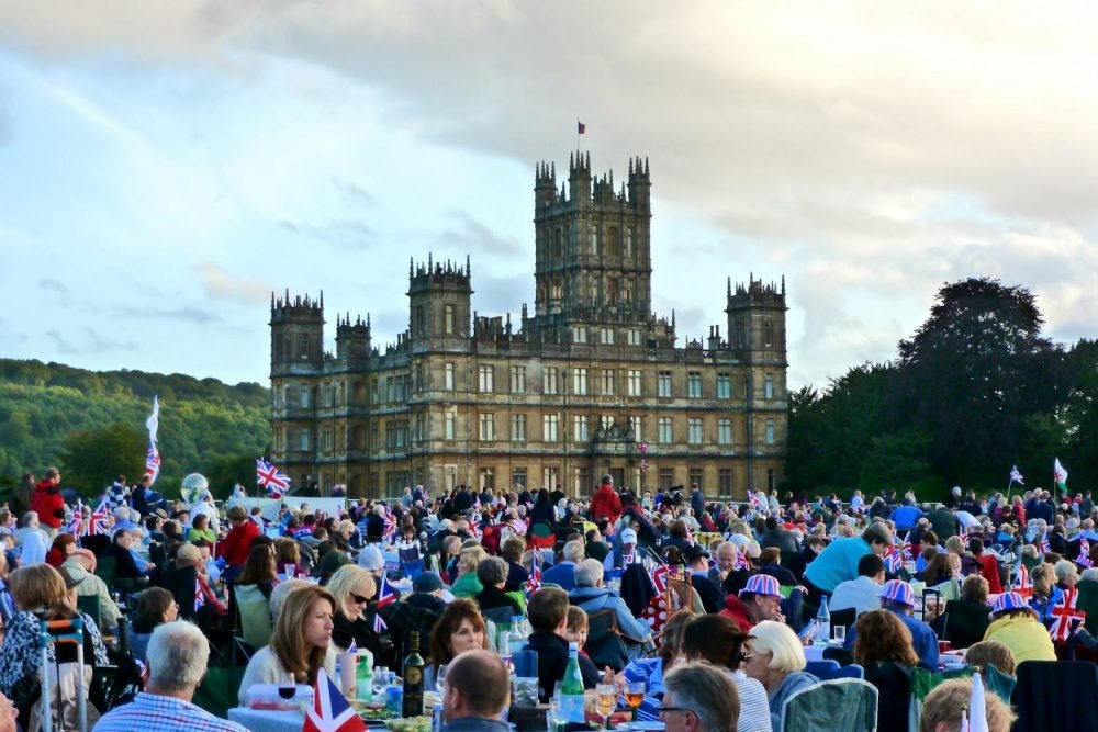 crowds of people waving flags gather in front of the palatial stately home Highclere Castle