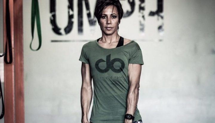 Dame Kelley Holmes looking strong and empowering wearing green workout t-shirt, black sports bra and black watch