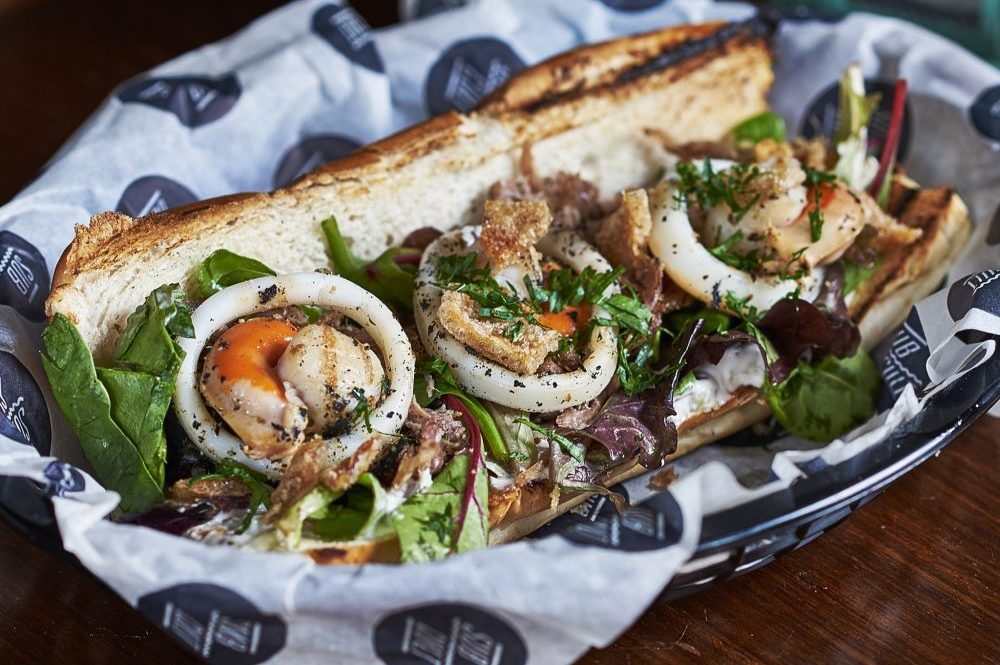 street food sandwich with seafood and salad wrapped in paper and served in a wire basket