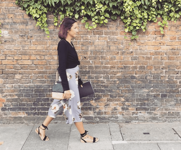 Lifestyle store owner Emma Bees of B The Lifestyle Store walking on a London street past an old back wall fringed with foliage