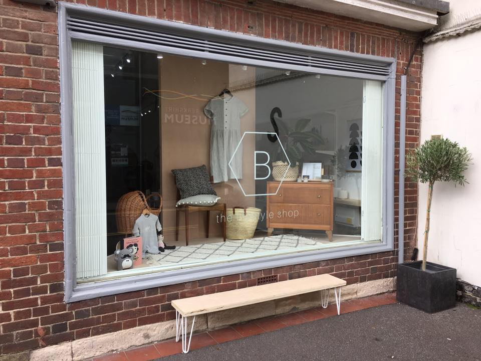 Large window in 1960s brick building showing a window display of Scandi design at B The Lifestyle Shop in Newbury, Berkshire