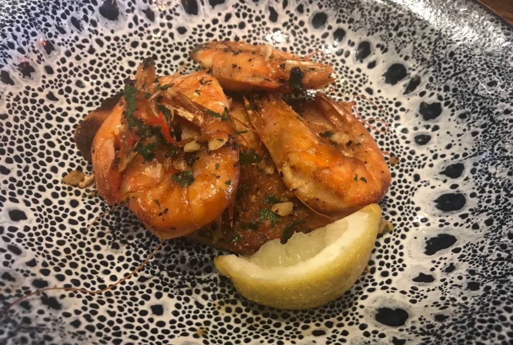 blue and white paint splattered plate with garlic and chilli prawns and a slice of lemon