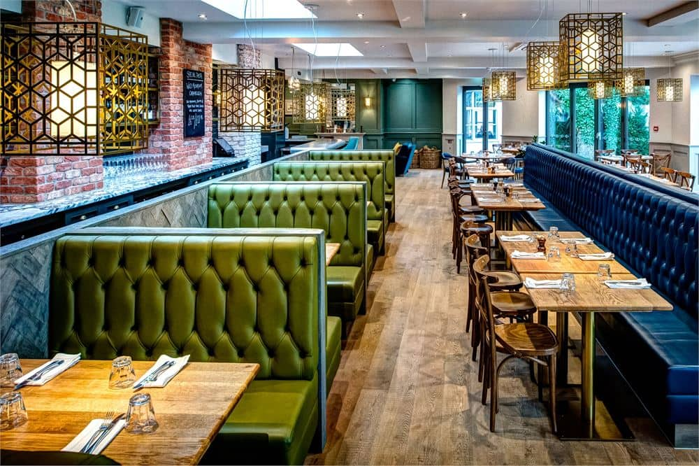 Coppa Club Sonning restaurant with green and blue leather banquettes, wooden floors and table with geometric brass lighting