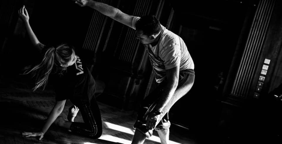 man and woman perform dance routine in black and white