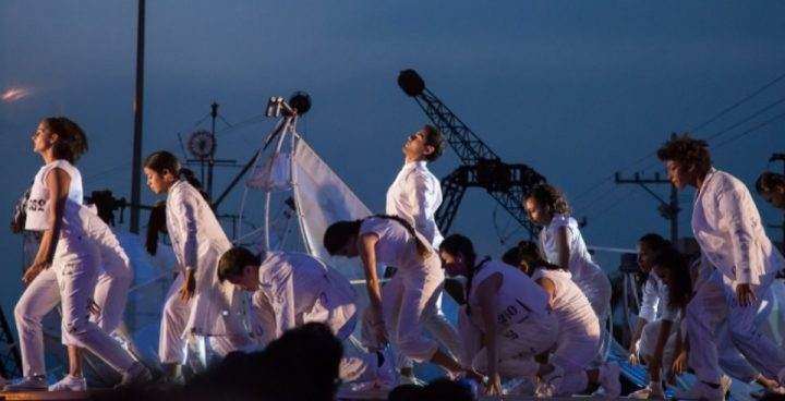 Dancers on a stag wearing white costumes with an industrial backdrop