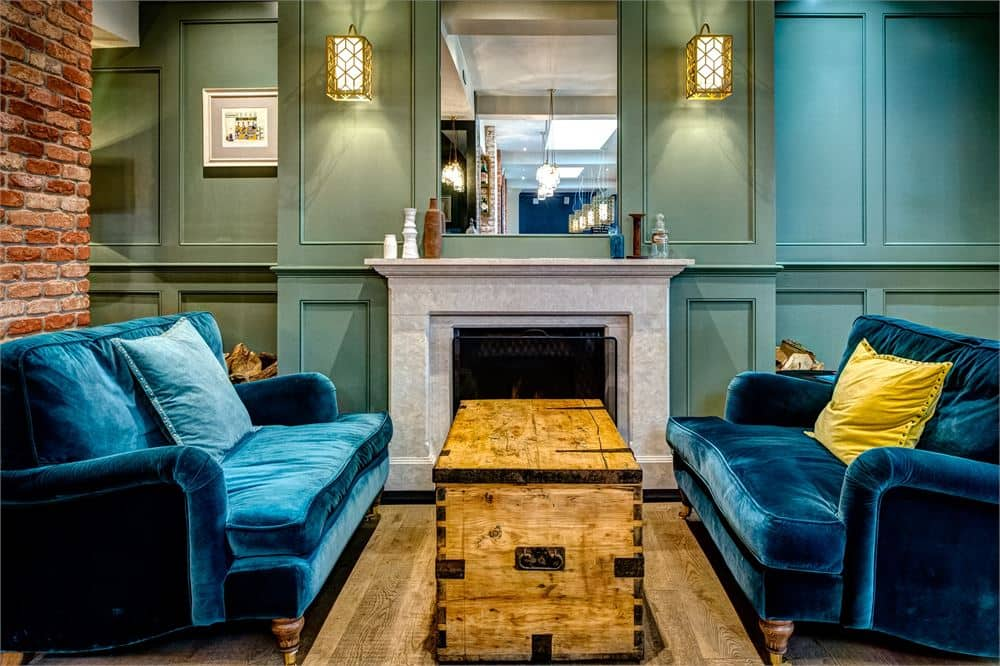 turquoise velvet sofas, pine trunk and stone fireplace and wooden floors with statement wall lights and blue walls