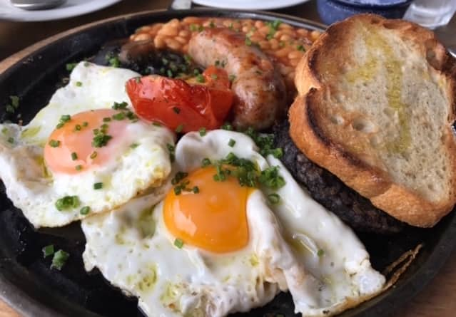 black cast iron griddle pan with a full english breakfast of eggs, bacon, sausage, tomatoes, baked beans, black pudding and sour dough toasted bread