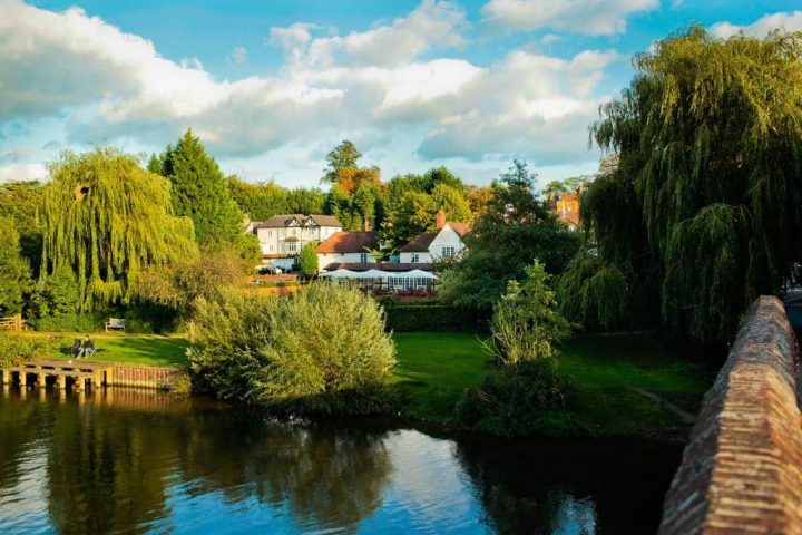 view of the large boutique hotel The Great House in Sonning from the banks of the river Thames surrounded by trees