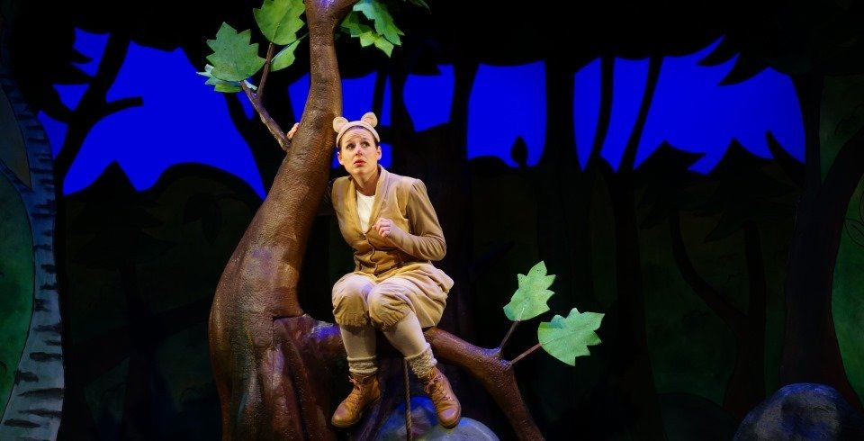 Stage production of The Gruffalo see the an actress dressed as a mouse sitting the tree os a dark wood on stage