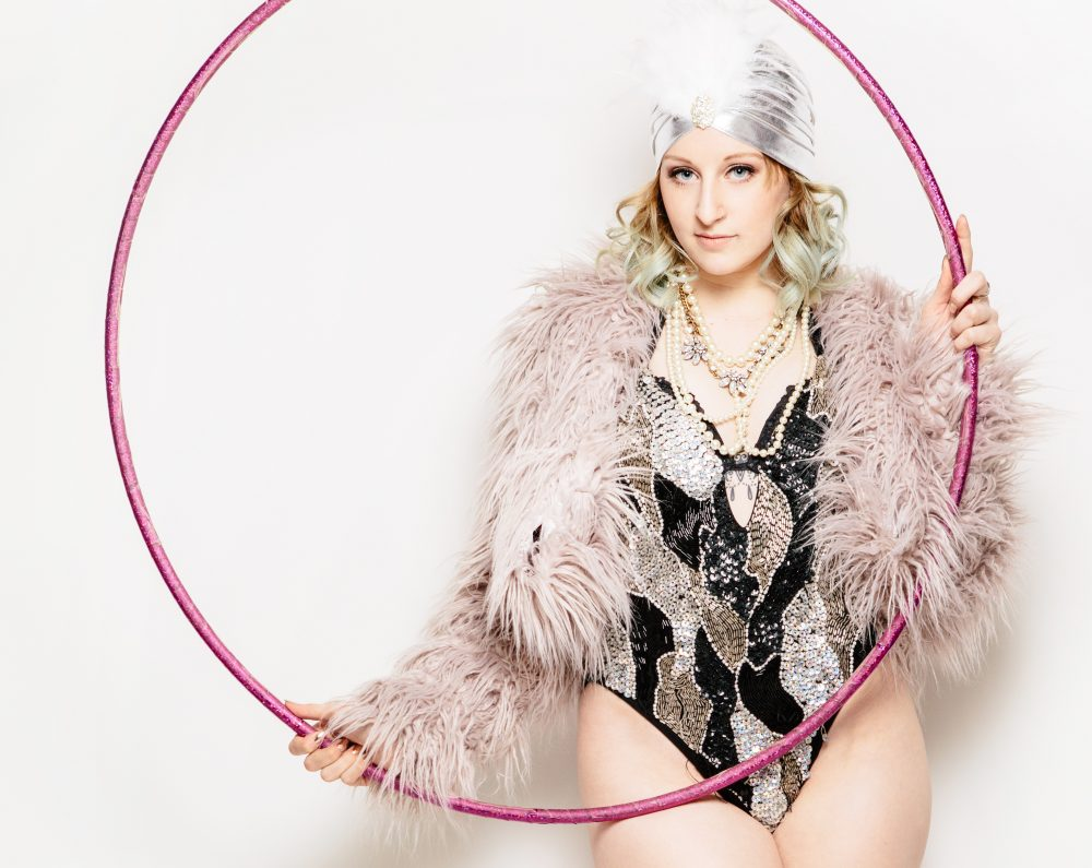 Burlesque dancer wearing a sequinned leotard, silver turban and pink feather jacket holding a large pink hoop