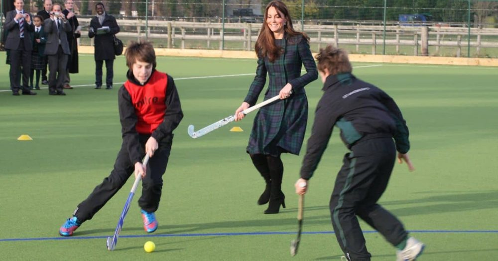 Duchess of Cambridge playing hockey on the astroturf pitch with kids from St Andrew's Pangbourne in plaid McQueen coat and heels.