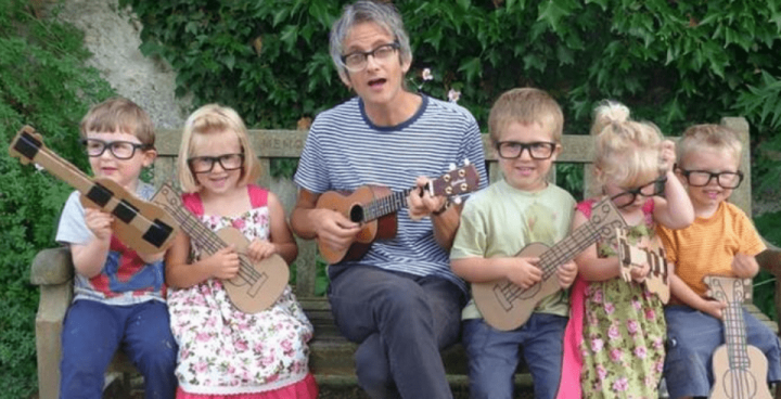 britpop musician Nick Cope playing the ukulele with spectacle wearing kids
