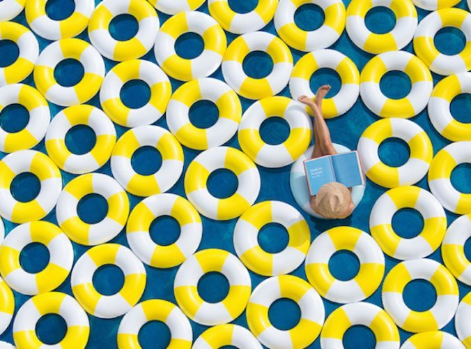 woman reading a book in a pool full of yellow and white rubber rings