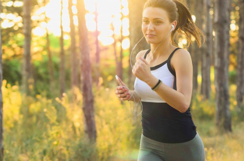 woman listening to music, and wearing running vest and leggings jogging through the woods