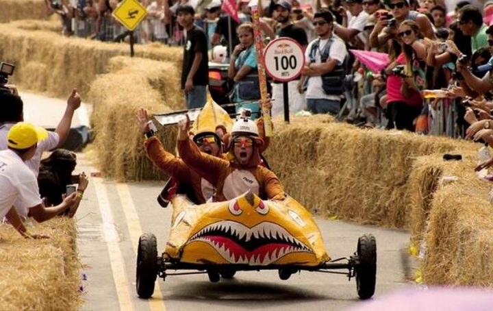 Soapbox kart decorated with like a banana with teeth driven by two men in bear costumes