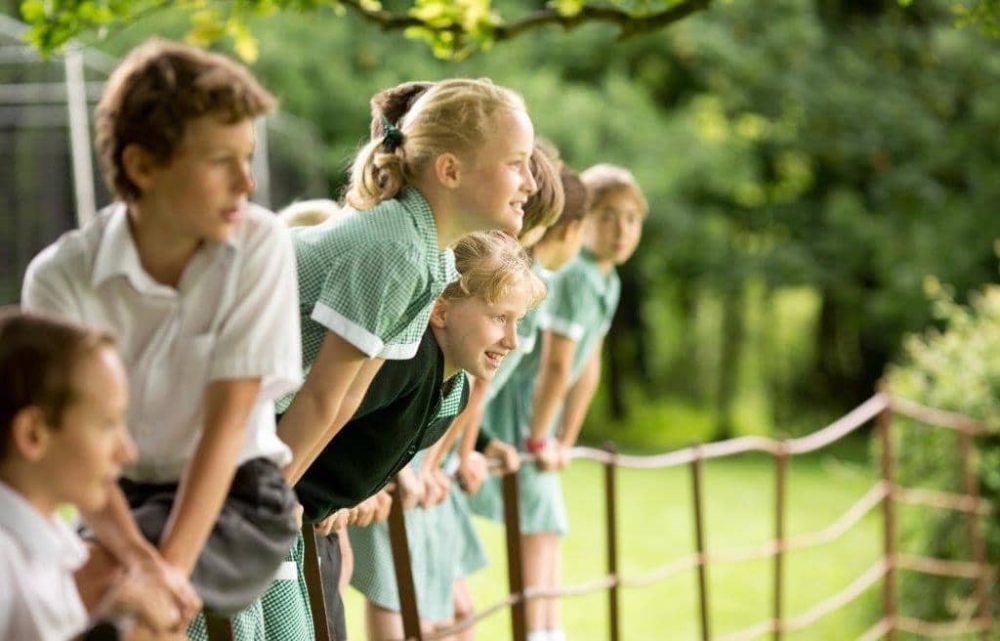 Boys and girls in green summer uniform enjoying the 54 acres of woodland at St Andrew's School Pangbourne
