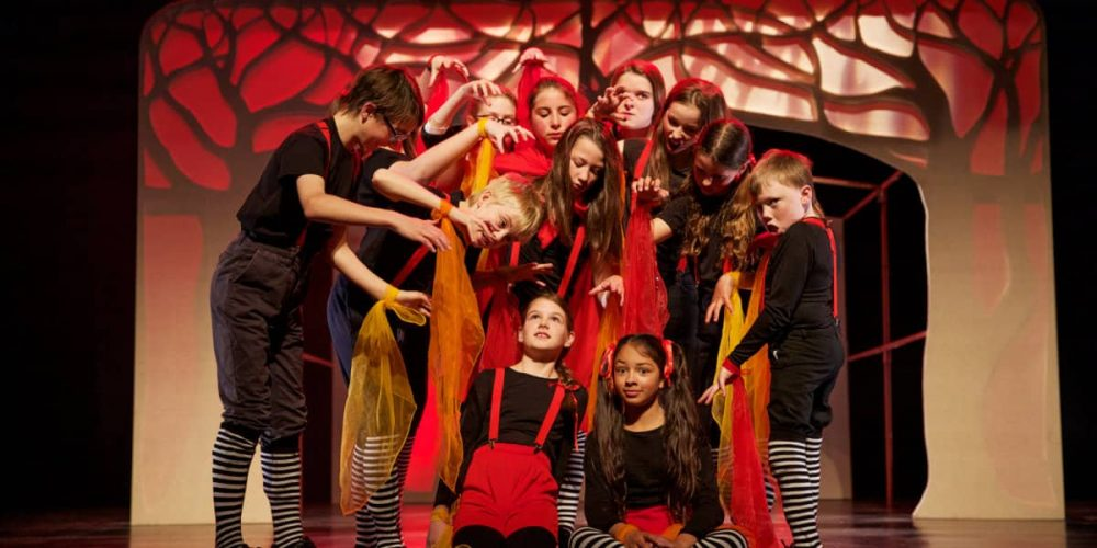 red and black staging of a youth theatre production at the Corn Exchange in Newbury