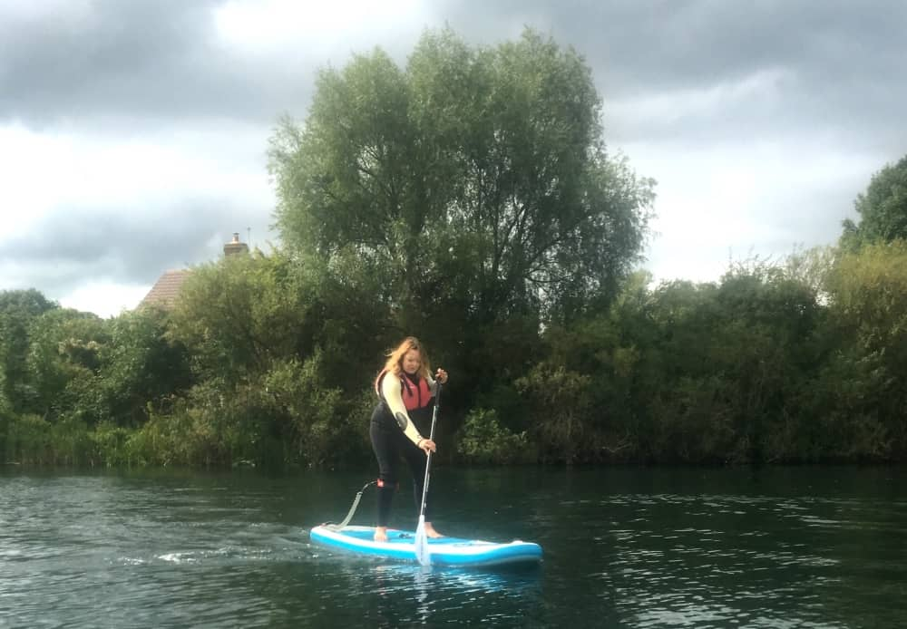 Wetsuit weather as Muddy Editor Rachel Jane paddle boards on a lake in Bray Berkshire