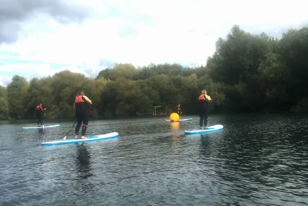 Four paddle boarders in a SUP class at Bray Lake Watersports