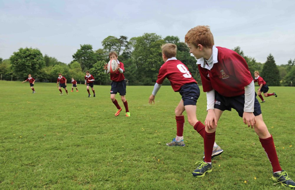 boys at brockhurst and marlston wearing their burgundy and black kit practice passing during rugby