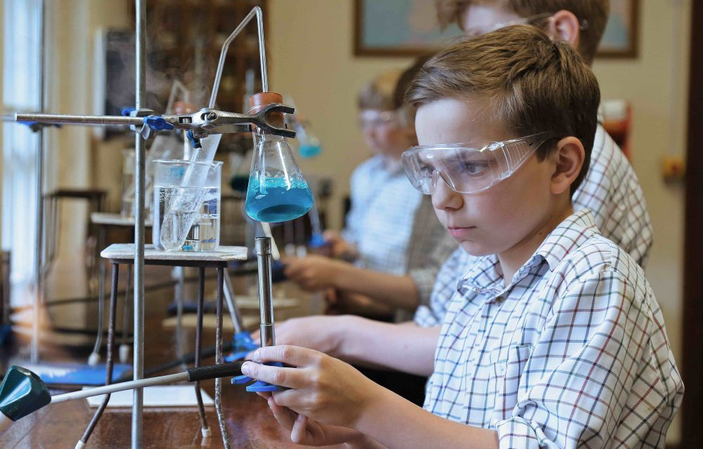 a child in his check shirt uniform doing an experiment with his bunsen burner in the science lab at Brockhurst and Marlston School