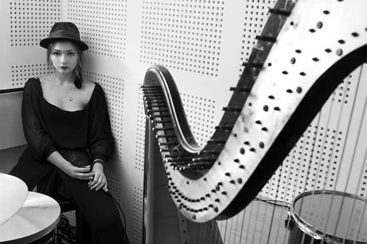 young woman wearing a hat and black in a studio with her harp in black and white