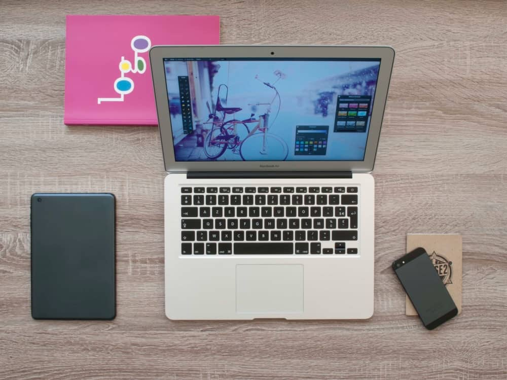 Home working flat lay – laptop, phone, tablet and pink notebook