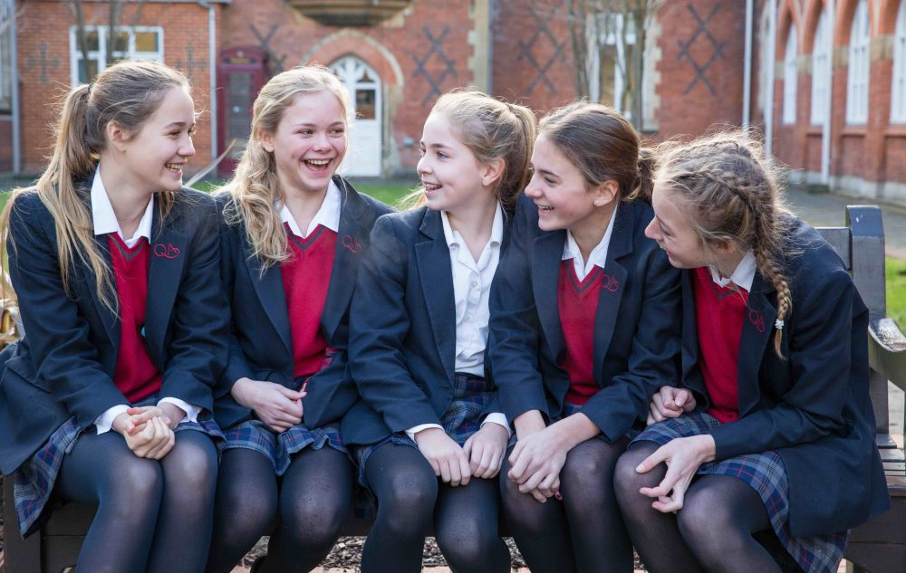 Queen Anne's girls enjoying school life wearing tartan skirts, red sweaters and blazer
