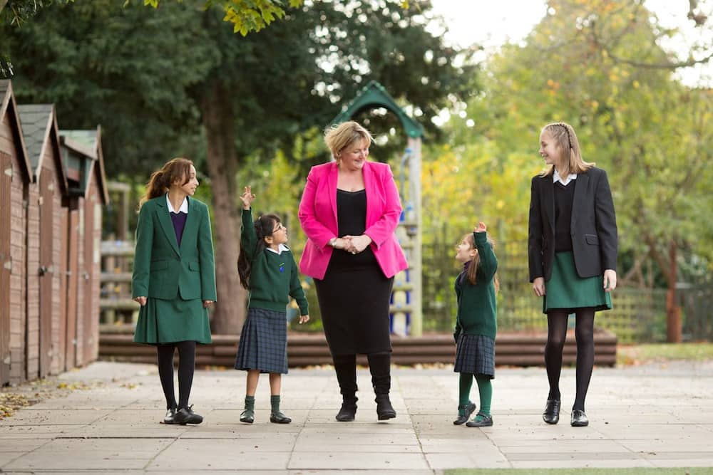Wearing bright pink jacket The Abbey School in Reading Head Rachel Dent with four of the pupils