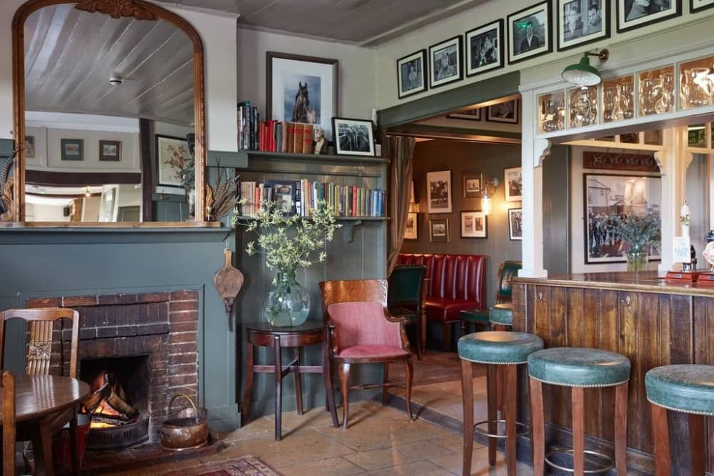 stone floor, dark walls and leather banquettes create the relaxed cosy country pub vibes at The Pheasant nr Hungerford