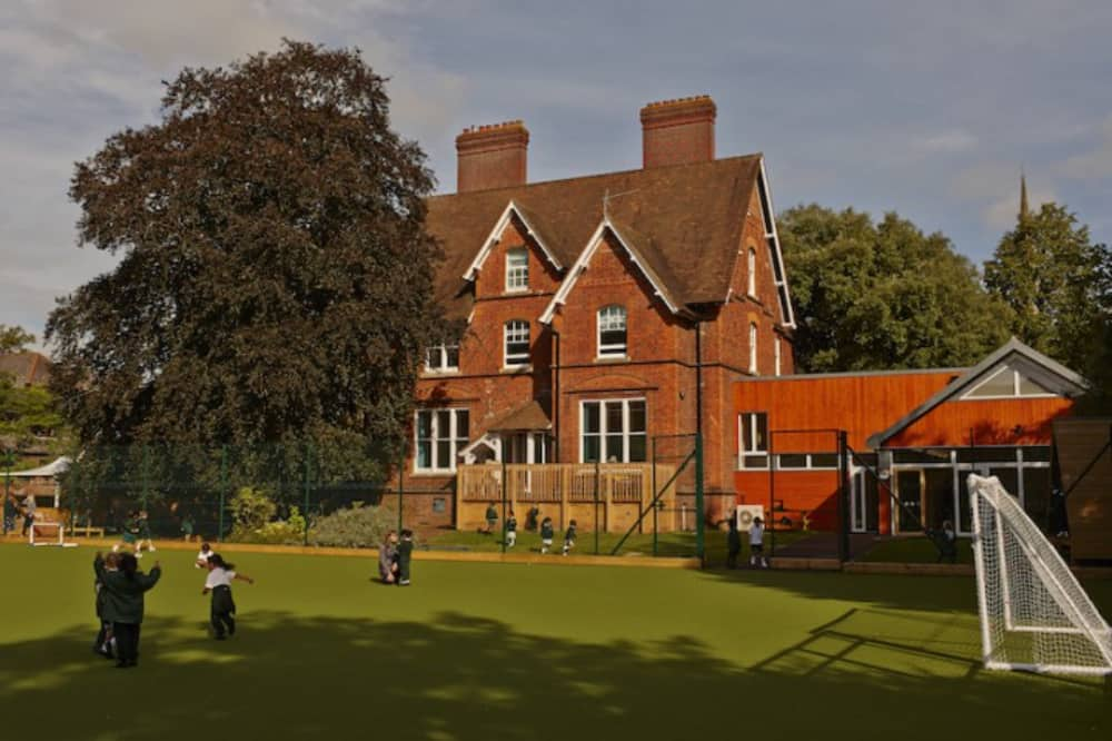 Astroturf pitch outside the red brick Victorian villa of The Abbey School in Reading