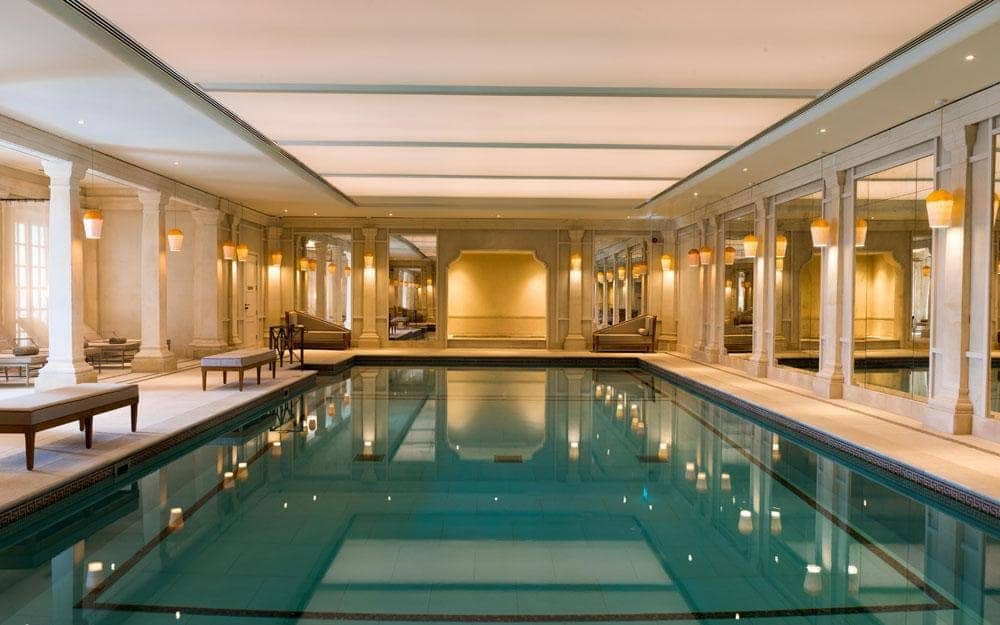 indoor pool at Cliveden House Spa surrounded by stone pillars, antiqued mirrors and elegant lighting
