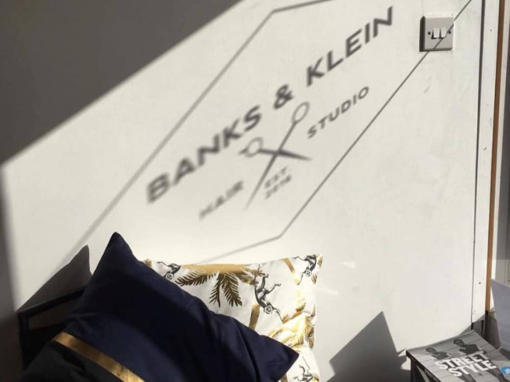 Reflection of the Banks and Klein Haire Studio logo against the wall of this Newbury boutique salon