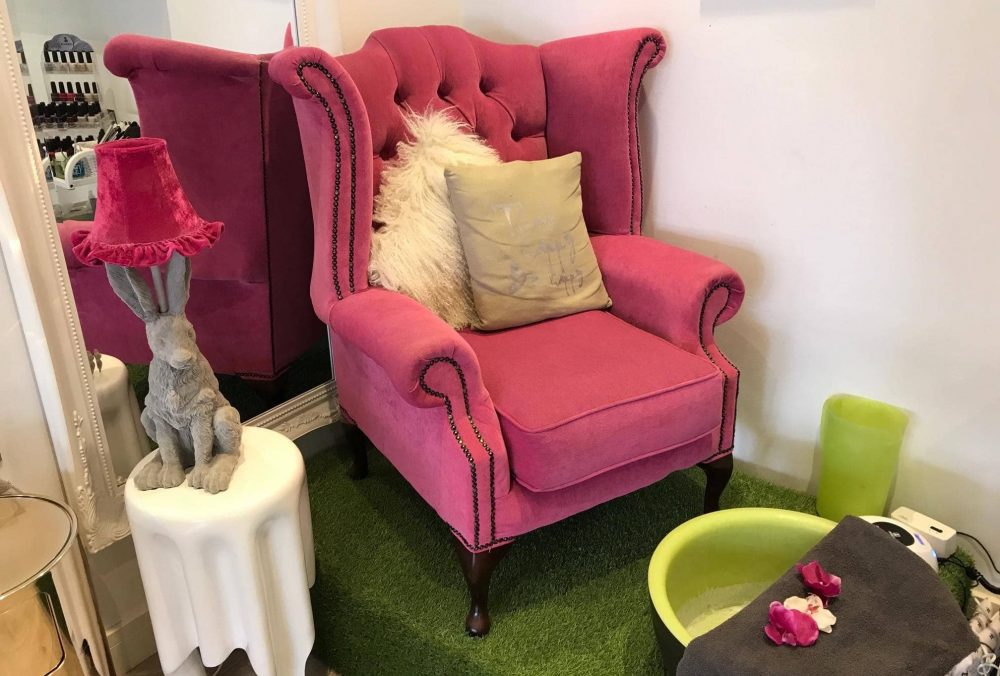 Quirky pedi plinth with fake grass, hot pink button backed chair and rabbit table lamp