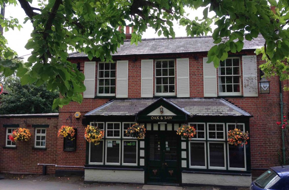Red brick Victorian pub with stylish green-grey shutters and the Oak & Saw in Taplow's award winning hanging baskets