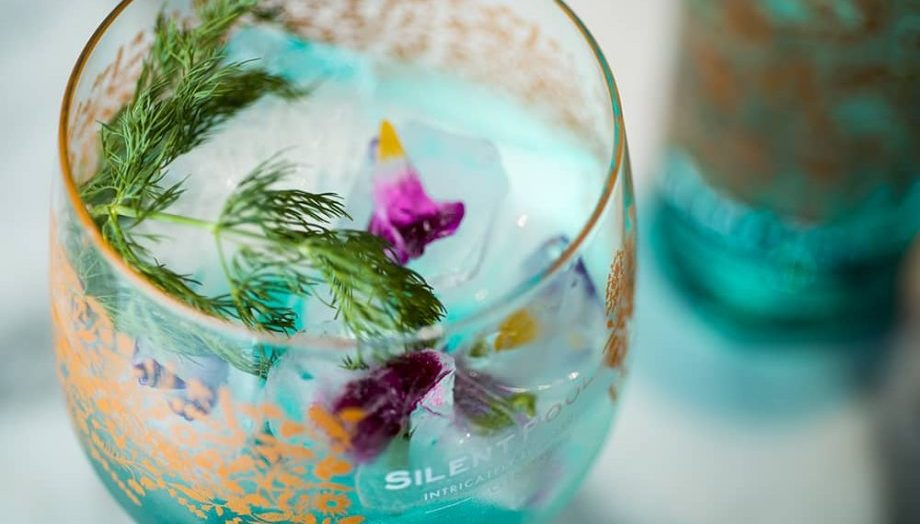 large bowl like glass of gin with herbs and flower decoration – Silent Pool gin