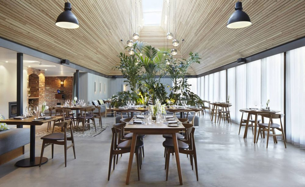 contemporary meets country wth stone floors and architectural wood ceiling with a wall of glass at the modernised Michelin star restaurant The Woodsmen near Newbury