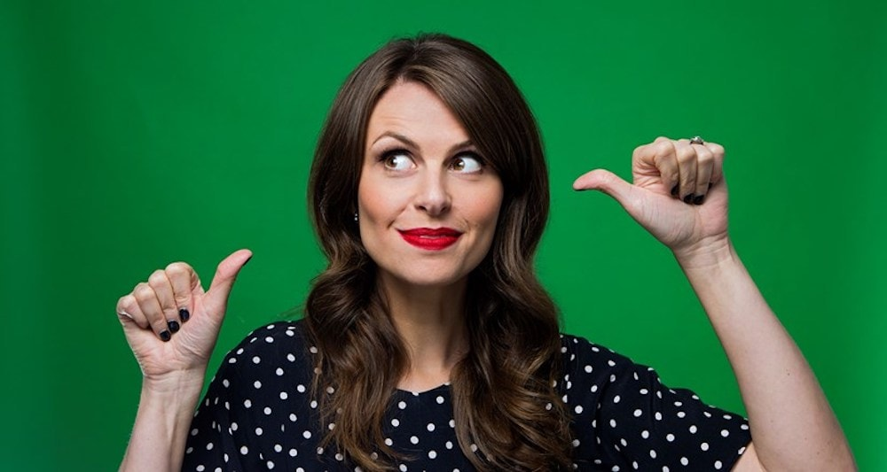 Comedian Ellie Taylor on tour wearing black and white polka dot dress and red lipstick