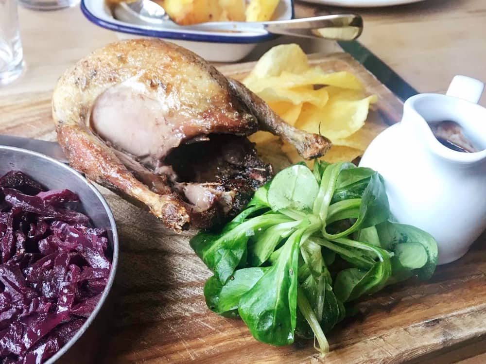 Roasted partridge with crispy roast potatoes, braised red cabbage and watercress served on a wooden board